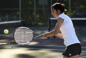 Kaya Pagano of Syracuse East returns against Eve Llanos of Syracuse West during their girls tennis match held at Corcoran High School. Photo by John Berry
